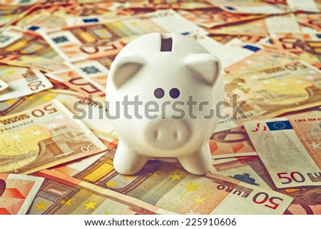 Piggy Coin Bank standing on fifty Euro banknotes pile as home budget theme illustrative image.