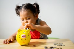 Piggy money box has big smile when blurry cute little girl put coin into it.Concept learning financial responsibility and planning saving up money.Insurance savings plans.