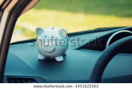 Piggy money box inside a car transportation. Saving money for vehicle purchase. Successful financial planning and banking concept. Economic investment for future. Dealership offering credits. #1411622363