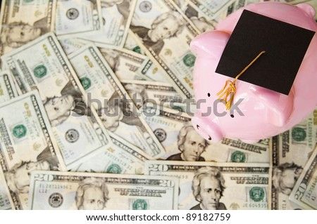 piggy with graduation cap on money
