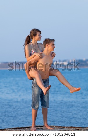 Piggyback. Attractive guy and girl are playing at the sea in evening time