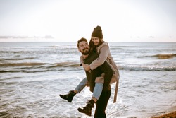 Piggyback couple at the beach celebrating their honeymoon at the winter time.