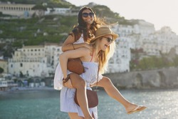 Piggyback happy tourist friends having fun on summer travel adventure vacation laughing
