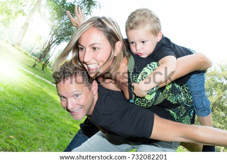 piggyback portrait of a cute family at nature #732082201