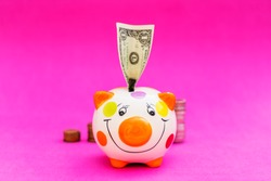 Piggybank and money tower , to save , saving money for affordable things, financial concept .Piggybank or deposit box on a wood background, depict saving money to make a trust fund for children, teach