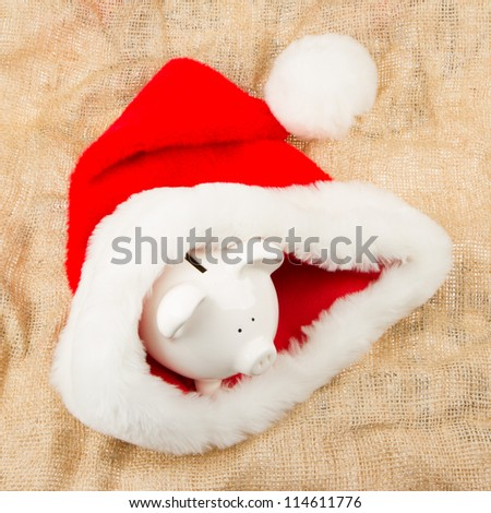 Piggybank guarding Santa's crisis budget, one dollar in his hat
