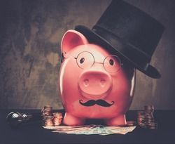 Piggybank in glasses and hat with pile of coins and banknotes