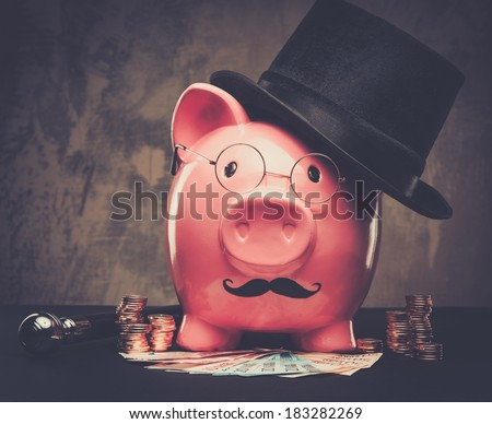 Piggybank in glasses and hat with pile of coins and banknotes  #183282269