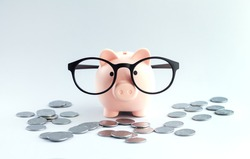 Piggybank wearing eyeglasses on office table with heap of coins. Saving money or savings concept