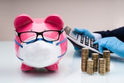 Piggybank With Face Mask During Coronavirus Pandemic Near Accountant