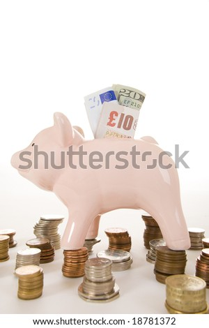 Piggybank with various countries currencies on white background, signifying the major currencies. Dollar, Euro and Pound Stirling is visible with coins from all over the world.