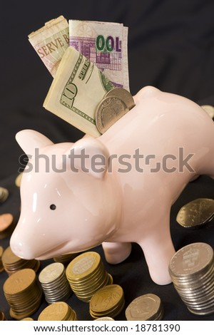 Piggybank with various international currencies on a black background.