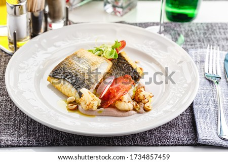 Photo of  Pike perch fillet with chorizo, cauliflower and radish in a restaurant serving