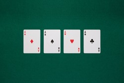 pikes card, cloves card, tiles card and hearts card on poker table green