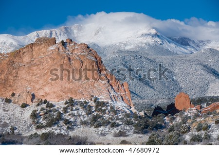 Pikes Peak covered by a white fluffy cloud in February as seen from the Garden of the Gods Park near Colorado Springs, Colorado.