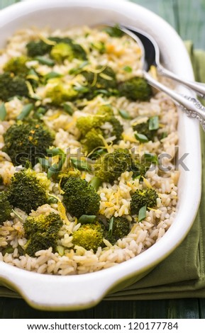 Pilaf with broccoli and lemon peel on green table