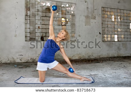Pilates exercise / Beautiful blond woman exercises with a fitness balls in an abandoned house
