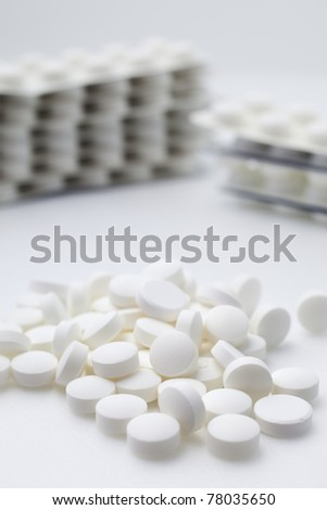Pile and stacks of white tablets on white background. - stock photo
