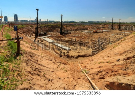 Pile driving in foundation pit construction apartment building. Piling driven ground. Deep foundation installation. Reinforce prestressed concrete piles factory foundation construction  #1575533896
