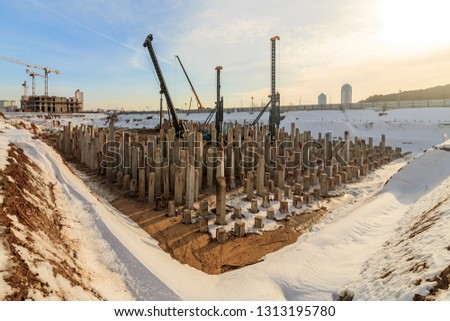 Pile driving in foundation pit for construction of apartment building. Piling driven into ground. Deep foundation installation. Reinforce prestressed concrete piles for factory foundation construction #1313195780