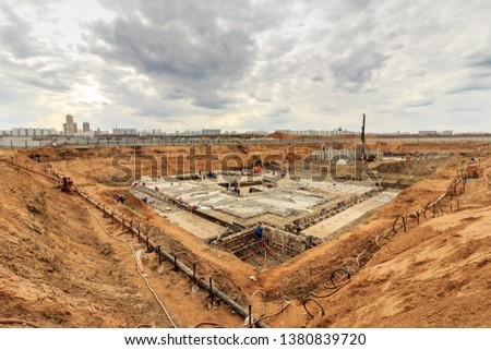 Pile driving in foundation pit for construction of apartment building. Piling driven into ground. Deep foundation installation. Reinforce prestressed concrete piles for factory foundation construction #1380839720