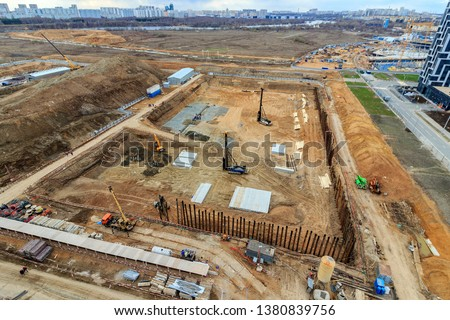 Pile driving in foundation pit for construction of apartment building. Piling driven into ground. Deep foundation installation. Reinforce prestressed concrete piles for factory foundation construction #1380839756