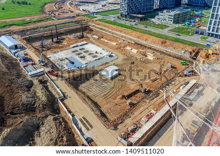 Pile driving in foundation pit for construction of apartment building. Piling driven into ground. Deep foundation installation. Reinforce prestressed concrete piles for factory foundation.  #1409511020