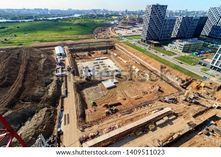 Pile driving in foundation pit for construction of apartment building. Piling driven into ground. Deep foundation installation. Reinforce prestressed concrete piles for factory foundation.
