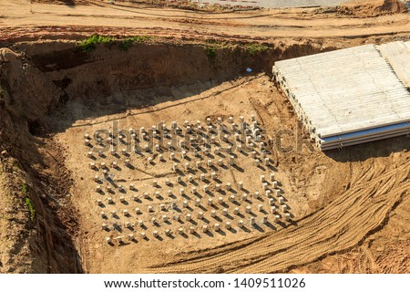 Pile driving in foundation pit for construction of apartment building. Piling driven into ground. Deep foundation installation. Reinforce prestressed concrete piles for factory foundation.  #1409511026