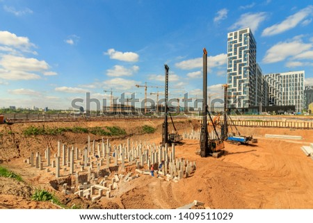 Pile driving in foundation pit for construction of apartment building. Piling driven into ground. Deep foundation installation. Reinforce prestressed concrete piles for factory foundation.  #1409511029