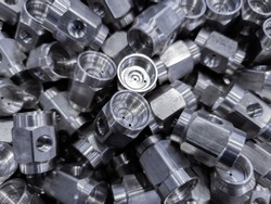 pile of abstract industrial close-up full frame background of shiny steel turned hexagonal parts