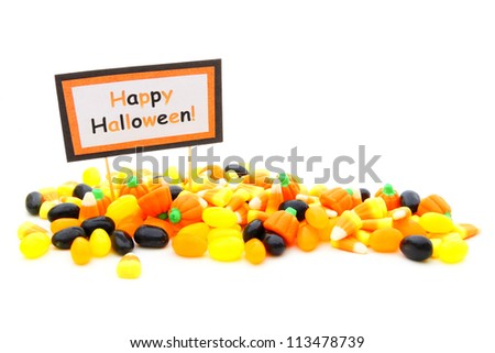 Pile of assorted Halloween candy with Happy Halloween tag over white