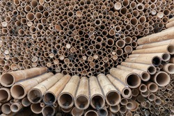 Pile of bamboo pole used in construction industry, bamboo wall textured background