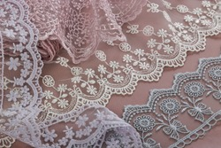 pile of beige, purple, white, gray gentle guipure, lace fabric on brown background. use for atelier. hygge champagne set sail concept.