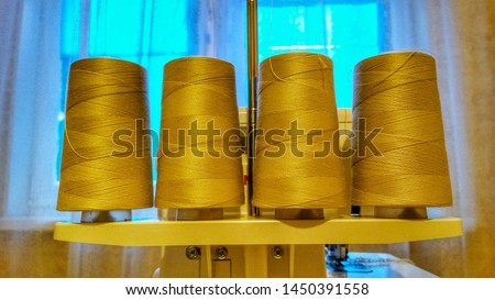 Pile of big beige color spools of thread. Concept fashion DIY clothing sewing handicraft design handmade tradition. Spools of thread are located on the sewing machine  #1450391558