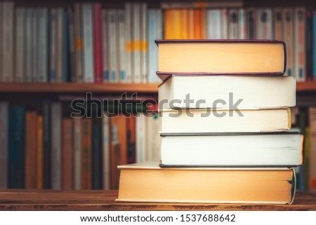 Pile of big books with blurry bookshelf in the background and copy space. Knowledge, reading, study, literacy or literature illustrative concept. #1537688642