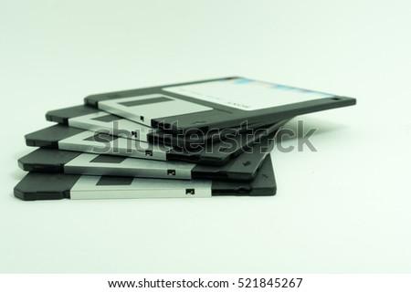 Pile of black floppy disks (diskette) on white background.