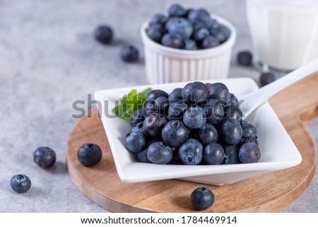 Pile of blueberry fruit in a bowl plate on a tray over gray cement concrete background, close up, healthy eating design concept. Stockfoto ©