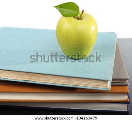 Pile of books and apple.