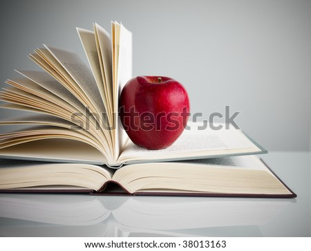 pile of books and red apple on desk. Copy space
