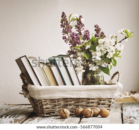 Pile of books and spring flowers of a lilac and apricot in a basket on a wooden surface. Vintage still life.
