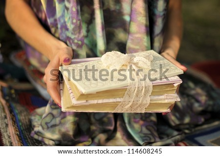 Pile of books in hands. Book with a white envelope tied with lace ribbon