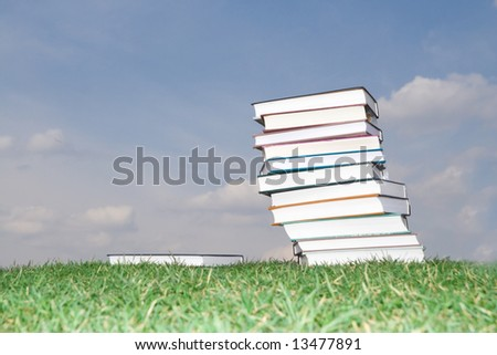 Pile of books laying on a grass