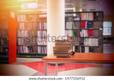 Pile of books on study desk in a study room. Education or academic concept picture of self access learning environment background related to research or reading materials, back to school concept