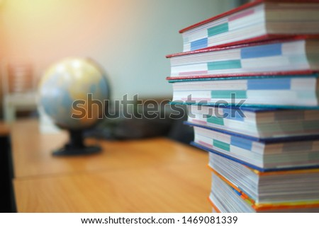 Pile of books on study desk with globe ball on the background, education or academic concept picture image of teaching and learning materials in high school, college or university campus, library room