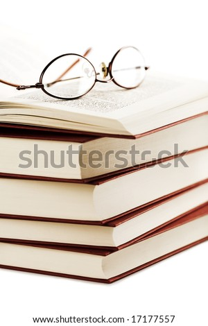 pile of books with glasses over it