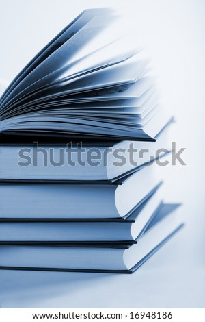 pile of books with one book open