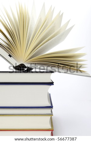 Pile of books with one book open, on white background