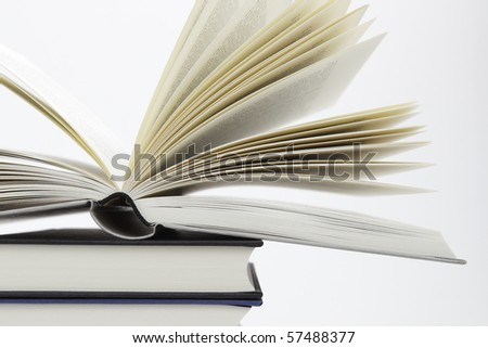 Pile of books with one book open, on white background - stock photo