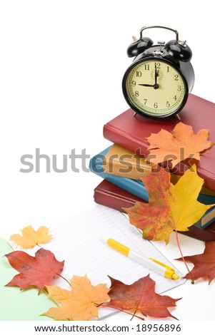 """Pile of books, writing-book, pen, alarm clock and autumn leaves on a white background. Concept for """"Back to school"""""""